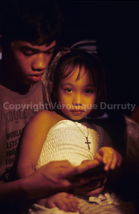 TAKING CARE OF HIS LITTLE SISTER. MANILLA, LUZON, THE PHILIPPINES