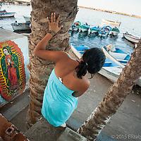 Una jóven se acerca al puerto de Santa Rosalía por la tarde a despedir a su novio que inicia su jornada de pesca de calamar.