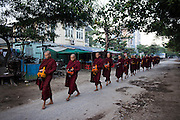 Novices and monks collecting alms in Mandalay, Myanmar.