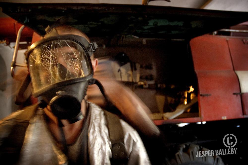 Moldawien, Republik Moldau, Stadt Soroca, Feuerwache, Feuerwehrmann setzt seine Atemschutzmaske auf. Das Glas ist gesprungen, doch das ist die einzige Maske, die er besitzt.Moldova, Soroca, Fire Station. Firefighter tries out his firefighter mask. The glass is broken but it is the only one he has, 05/2005 © 2010 Jesper Balleby / Agentur Focus