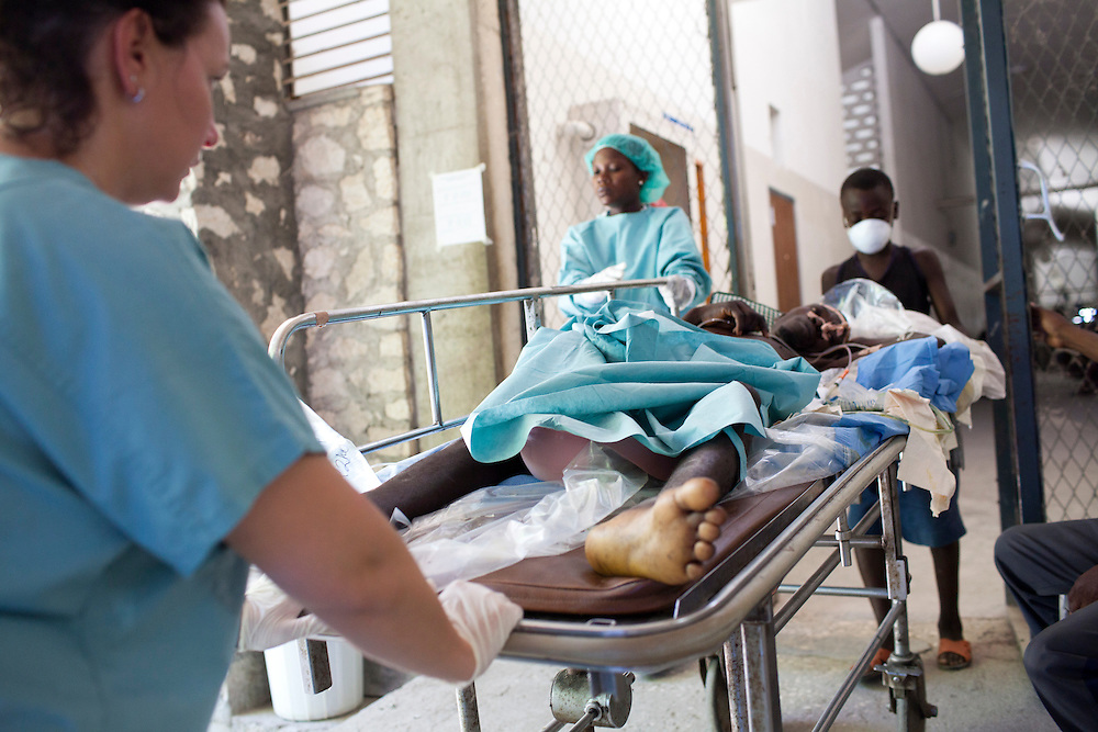 Project HOPE volunteer nurse Alysia Monaco, left, helps move a cholera patient back to his place after receiving X-rays on at the Hospital Albert Schweitzer on Friday, October 29, 2010 in Deschapelles, Haiti.