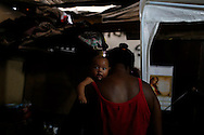 """A babysitter holds a baby at her makeshift home, part of the Nova Tuffy slum, in an abandoned factory in Rio de Janeiro, October 17, 2014. Since seven months ago, 1,800 families have been living inside the factory, which they occupied in March, with poor sanitation services and the fear of eviction. The occupants of the factory say they are not included in the housing program """"Minha Casa, Minha Vida"""" (My House, My Life), and they would like to be included by the Brazilian government. The housing program is one of several government initiatives aimed at reducing poverty and social inequality that President Dilma Rousseff has held up as achievements of her administration as she campaigns for re-election. Photo/Pilar Olivares"""