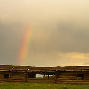 A bright rainbow falls on the roof of the Cunningham Cabin, a historic feature of the Grand Teton National Park in Wyoming. The cabin was build in 1890 by Pierce and Margaret Cunningham as part of a 160 acre homestead.