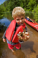 A 5 year old boy on kayak outing at Walden Pond picks up a crayfish.