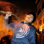 Night celebrations in the street.A child hits himself whit the chains in sign of mourning....