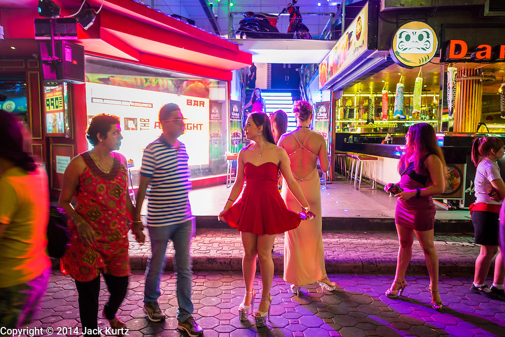 "26 SEPTEMBER 2014 - PATTAYA, CHONBURI, THAILAND: People in front of a go-go bar that advertises dancers from Russia on Walking Street in Pataya. Pataya, a beach resort about two hours from Bangkok, has wrestled with a reputation of having a high crime rate and being a haven for sex tourism. After the coup in May, the military government cracked down on other Thai beach resorts, notably Phuket and Hua Hin, putting military officers in charge of law enforcement and cleaning up unlicensed businesses that encroached on beaches. Pattaya city officials have launched their own crackdown and clean up in order to prevent a military crackdown. City officials have vowed to remake Pattaya as a ""family friendly"" destination. City police and tourist police now patrol ""Walking Street,"" Pattaya's notorious red light district, and officials are cracking down on unlicensed businesses on the beach.     PHOTO BY JACK KURTZ"