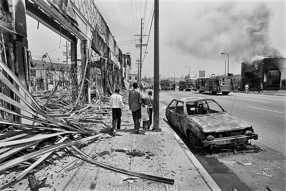 A group of children walk by riot damaged businesses on W.Adams Blvd. in South Los Angeles. 5/1/1992<br /> <br /> 25 before and after LA92 photo project.