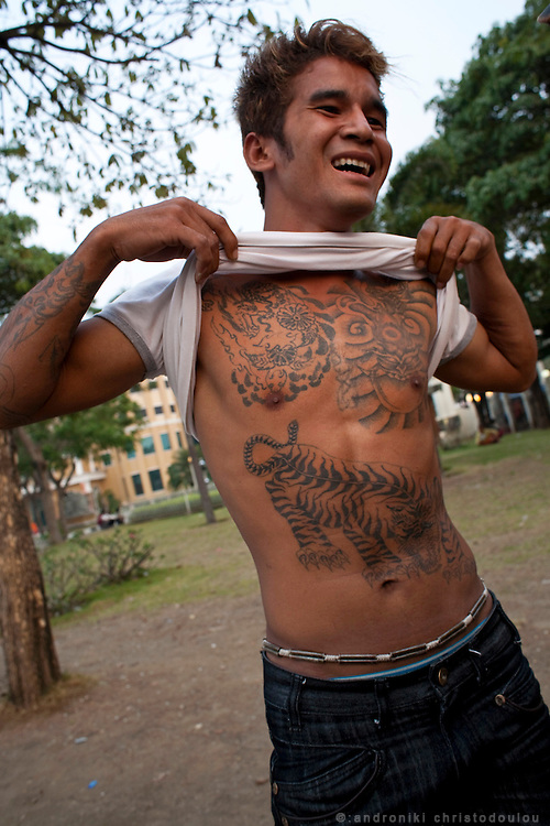 Moto-taxi driver displaying his tattoos..In the no-mans-land  between the border of Thailand and Cambodia near the Thai border town Aranyaprathet, there is a cazino town where mainly Thai customers go for a day or two to visit any of the 8 fancy cazinos there. At the same time, every morning Cambodian people cross the border on foot to go to their jobs in Thailand and the come back in the evening. Goods are also transported on wooden handheld carriages from one side to the other, passing through the Khmer gate that lays in the middle.