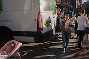 A baby sleeps and a woman carries her pet dog through rush-hour crowds at London Bridge in Southwark, south London.