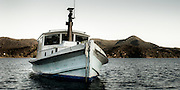 Old wooden launch at anchor in Tryphena Harbour, Great Barrier Island, New Zealand.