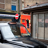Taxi passes a man putting up a street sign in the trendy Brick Lane area of Shoreditch, London. UK..Photo@Steve Forrest/Workers' Photos