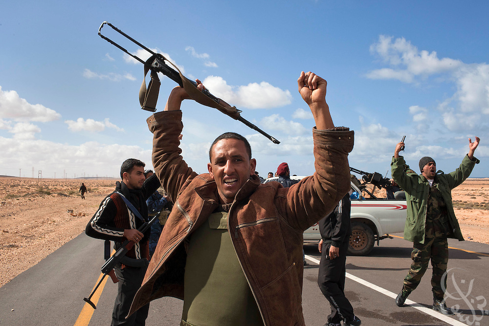 Libyan rebel fighters wave weapons s they celebrate their advance during a battle with pro-Qaddafi forces just outside the coastal town of Bin Jawwad. Rebels fought pro-Qaddafi forces there throughout the day as they tried to regain control the town from government forces that seized the town overnight.
