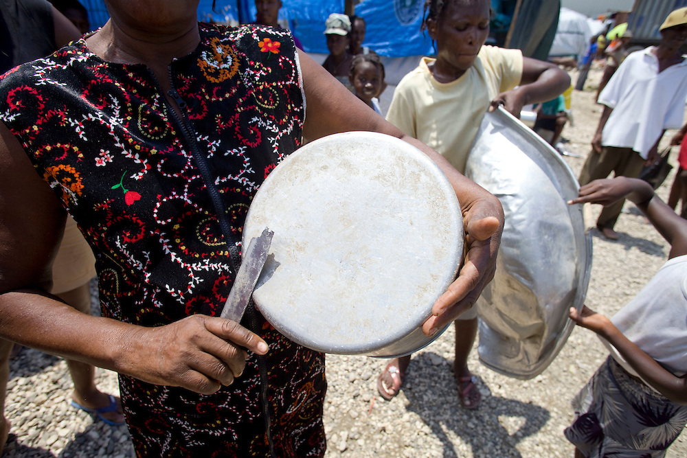 """Camp residents beat pans and scraps of metal in protest of forced evictions. Fifteen camps threatened with forced expulsion all over Port-au-Prince  simultaneously beat pots and pans, or """"bat teneb,"""" demanding a moratorium on expulsions and an immediate solution to inadequate shelter while hurricanes loom..The groups' press release says, """"The government must immediately provide humane alternatives to the muddy, dangerous, unsanitary and brutal living conditions by verifying ownership titles, and nationalizing by decree all empty and idle lands in the hands of large landowners... We refuse to participate in your election while under tarps, while being evicted from tents, without respect for our basic rights. We're asking for houses, to which we have a right. This is no gift, it is our right under article 22 of the March 29, 1987 Constitution, which guarantees the Haitian state provide decent lodgings to all its citizens."""".""""The law is perfectly clear,"""" according to human rights attorney Mario Joseph. """"There is a problem of political will and a problem of exclusion. The poor have been excluded from their land for years, and are now excluded from the process determining their rights to lodgings."""""""