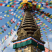 """Kathesimbhu means """"Kathmandu Swayambhu"""". This 17th century stupa (bell-shaped Buddhist monument) in Kathmandu, Nepal, is a smaller version of the more famous """"Monkey Temple"""" at Swayambhu. A walk around the Kathesimbhu stupa promises the old and lame the same blessings as a pilgrimage to Swayambhunath's hill. Buddha Eyes gaze from one side of Swayambhunath, the """"Monkey Temple"""". On most every stupa (Buddhist shrine) in Nepal, giant Buddha Eyes (or Wisdom Eyes) stare from four sides of the upper cube. These four directions symbolize the omniscience (all-seeing) of a Buddha. The third eye (above and between the other two eyes) also symbolizes the all-seeing wisdom of the Buddha. The curled symbol (shaped like a question mark) in place of a nose is the Nepali character for the number 1, which symbolizes unity of all things."""