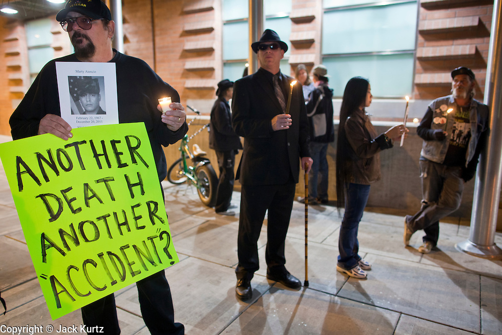 """04 JANUARY 2012 - PHOENIX, AZ:    TOM DYSON, left, CRAIG SLOMIN, KEN ALANDT and LOVELY DYSON during a vigil for Marty Atencio in front of the Maricopa County Jail in Phoenix on January 4. Atencio died in a Phoenix hospital on Dec 20, 2011. He was arrested by Phoenix police a few days earlier after he exhibited """"bizarre"""" behavior on the street. He was booked into the Maricopa County Jail. During the booking process he was tackled by Maricopa County Detention Officers and repeatedly hit was a Taser stun gun. He was later found unconscious in a holding cell and transferred to a hospital, where he died four days later. An autopsy showed no signs of illegal drugs or intoxication and a video from the jail showed that Atencio was not violent in the jail. His family has hired a lawyer and may sue the Maricopa County Sheriff's Department, which administers the jail.     PHOTO BY JACK KURTZ"""
