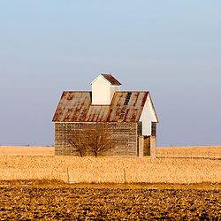 The low winter sun catches the dilapidated siding and roof of an old barn on the plains of central Illinois.