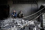 Gaza City: Palestinians sit on rubbles from their destroyed houses following overnight Israeli air strikes on the village of Beit Lahia in the northern Gaza Strip . November 18, 2012. ALESSIO ROMENZI