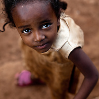Young girl in pink sandals looking up, Delo Mena, Ethiopia