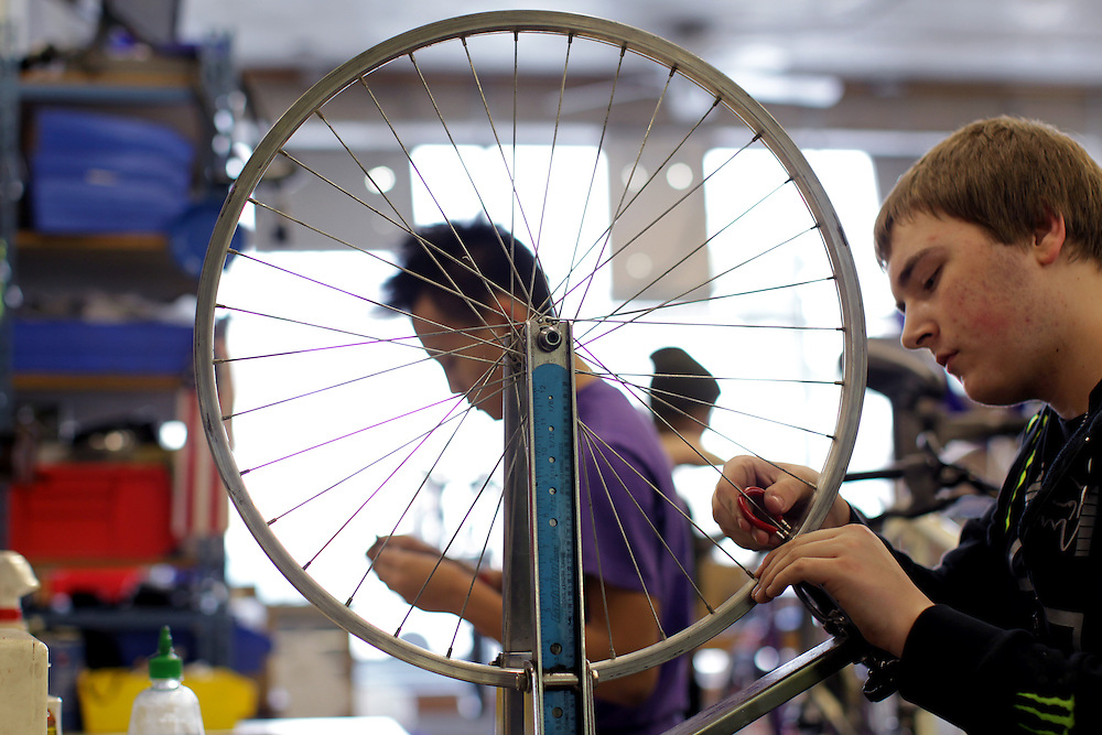 Youth Express apprentices Marcus Wachholz, 17, right, and Koua Yang, 15, work to straighten wheels on donated bikes at Express Bike Shop in St. Paul, Minnesota.  By refurbishing and selling bicycles, youth apprentices learn mechanical, business, and entrepreneurial skills.