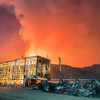 A burnt out semi truck, victim of the Blue Cur Fire, rests off Interstate 15 as the trailer contents burn while the fire continues to burn in the distance. The fire started under Red Flag Conditions with extreme heat and low humidity, leading to dangerous rates of fire spread during California's historic drought. The Interstate was closed to through traffic and thousands were evacuated in the area. <br /> <br /> The Blue Cut Fire burns in and around the San Bernardino National Forest in San Bernardino, CA August 16th, 2016. <br /> <br /> Long exposure image.