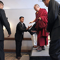 The Dalai Lama is helped down from a stage following a news conference at the Charles Hotel in Cambridge, Wednesday,  April 29, 2009.