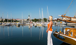 Woman standing at old sailing ship, Water, reflection. Tallinn cityscape and old city marina in Admiraliteet pool, Estonia.