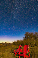 The iconic Parks Canada red chairs at the waterfowl viewing pond at the entrance of Waterton Lakes National Park, Alberta, Canada, on a moonlit autumn evening with the stars of the autumn sky rising in the northeast. Visible are Perseus, the W of Cassiopeia, and most of Andromeda, including the Andromeda Galaxy at upper right. The bright star at lower left is Capella in Auriga. <br /> <br /> The night was very windy, thus the blurred trees and bushes (there was no special lens blue filter applied!) in this 20-second exposure at f/2.8 and ISO 2000 with the Nikon D750 and Sigma 24mm lens, on a static tripod, no tracking. Light is from the First Quarter Moon.