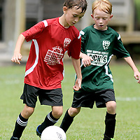 Quentin Hamilton, left, 8, dribbles past Logan Rogers, 8, during a Port City Soccer match Saturday September 6, 2014 at Olsen Farm Fields. (Jason A. Frizzelle)