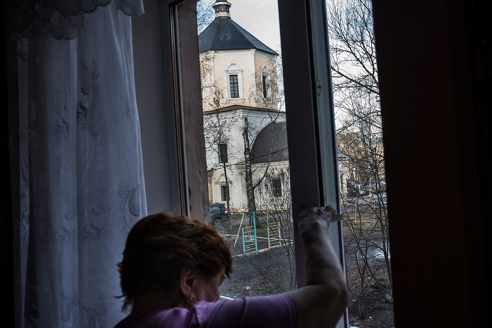 Nina Rozova, Alexander Panin's grandmother, opens a window with a view to a nearby church in her apartment where Panin was mostly raised on Tuesday, February 25, 2014 in Tver, Russia. Panin, a Russian citizen who was arrested in the Dominican Republic in June 2013, is set to be charged by federal authorities in the US with being part of a gang which robbed bank accounts via the Internet. Photo by Brendan Hoffman, Freelance
