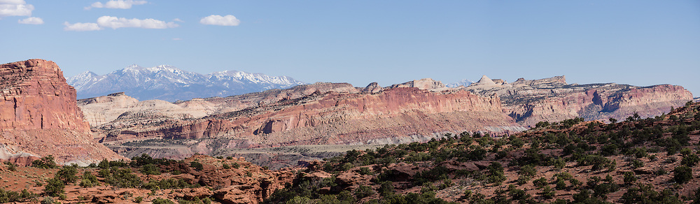 Capitol Reef National Park is centered upon the 100-mile-long Waterpocket Fold, the steep eastern limb of the Circle Cliffs Uplift, formed in Late Cretaceous time, during the Laramide Orogeny. Pressure caused by the subduction of the Farallon Plate beneath the North American Plate along the west coast caused several huge folds like this in southeast Utah, USA. Steeply tilted Triassic and Jurassic rocks form the hogbacks of the Waterpocket Fold and Capitol Reef, which is built of dark-red dune-formed Wingate Sandstone, thinly bedded river deposits of the Kayenta Formation, crested by the massive, white, dune-formed Navajo Sandstone. This panorama was stitched from 3 overlapping photos.