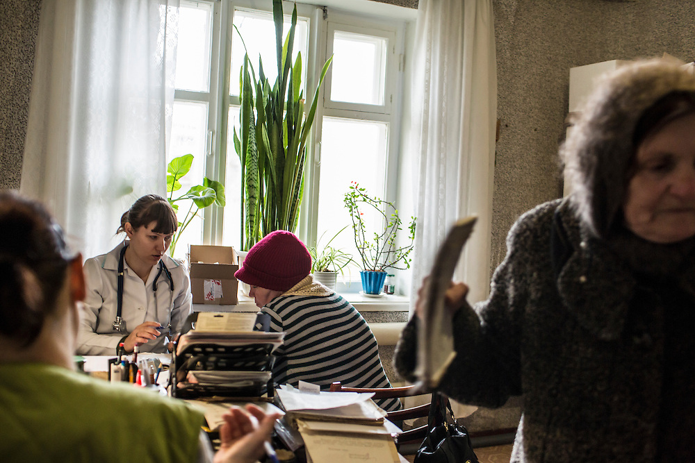 ZIMOGORYE, UKRAINE - MARCH 15, 2015: Yelena Beybudova, left, a nurse, and Yevgeniya Kovalenko, a general practitioner, second from left, consult with patients at the Zimogoryivskaya Ambulatory in Zimogorye, Ukraine. CREDIT: Brendan Hoffman for The New York Times