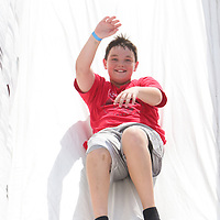 Kodie Shears, 10, slides Sunday August 17, 2014 during Ribfest Battleship Park in Wilmington, N.C. (Jason A. Frizzelle)