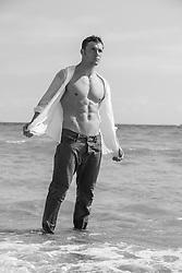 hot man taking off his shirt at the beach