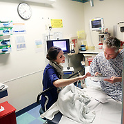 "Hannah Lobingier provides patient Robert Cooper with information on local clinics. Cooper came to the emergency room with chest pain and complaints of numbness that he had put off for a long time...""Typically, an ER is a Band-Aid on a condition; a car accident or some other trauma. But we're trying to see the whole picture of the patient. It's a real culture change. A lot of patients we see have never been told they have options in their care. A patient who comes in to the ER with a sore throat or ingrown toenail may not know how they can go to a community partner clinic or urgent care setting and save thousands of dollars."" - Hannah Lobingier...Hannah Lobingier and other patient guides in the emergency department at Providence St. Vincent Medical Center in Portland, Ore., are part of a new grant-based program in the Health Share CCO. Many people who come to the emergency room would be more appropriately served in less-expensive settings, and patient guides such as Lobingier act as advocates to help find these patients the appropriate care."