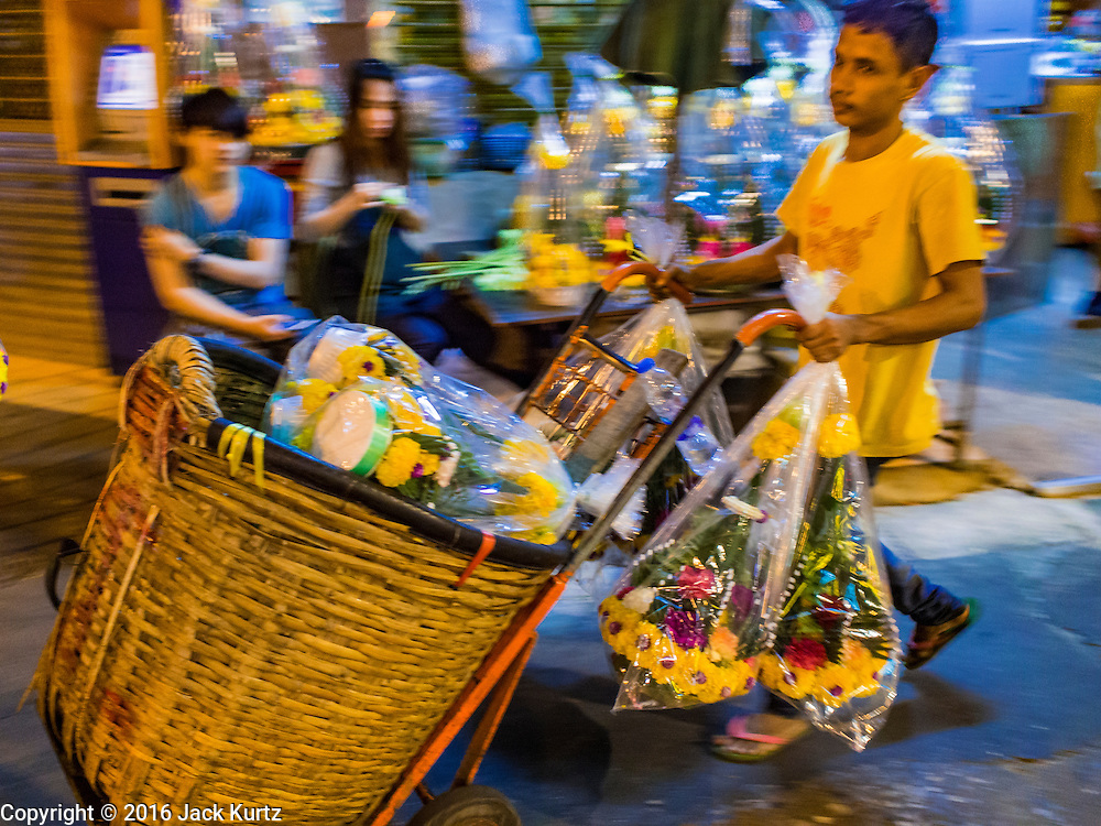 29 FEBRUARY 2016 - BANGKOK, THAILAND: A porter pushes baskets of flowers past the Bangkok flower market. Many of the sidewalk vendors around Pak Khlong Talat, the Bangkok flower market, closed their stalls Monday. As a part of the military government sponsored initiative to clean up Bangkok, city officials announced new rules for the sidewalk vendors that shortened their hours and changed the regulations they worked under. Some vendors said the new rules were confusing and too limiting and most vendors chose to close Monday rather than risk fines and penalties. Many hope to reopen when the situation is clarified.    PHOTO BY JACK KURTZ
