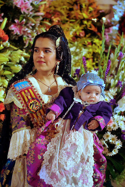 """las fallas festival in Valencia Spain. Las Fallas literally means """"the fires"""" in Valencian ..The biggest and most spectacular event is the Ofrenda de Flores a la Virgen de los Desamparados (a floral offering to our Lady of the Forsaken): On the 17th and 18th of March, from 4pm until nightfall, there is an enormous multi-coloured parade; with the members of the Fallas wearing their marvellous, intricately decorated, traditional costumes and carrying bunches of flowers as an offering to their Patron Saint. ."""