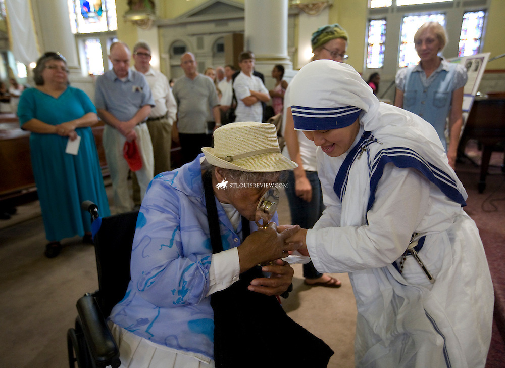 """Oralynn Allen, 84, kissed a relic of Blessed Teresa of Calcutta last week as it was held by a Missionaries of Charity nun at Sts. Teresa and Bridget Parish in North St. Louis. In 1978, Allen escorted Mother Teresa around St. Louis during a visit. """"We walked and walked all over St. Louis,"""" Allen said. For one afternoon, the Missionaries of Charity placed on display relics of Blessed Teresa's blood and hair, as well as several items she used during her lifetime. The itiems included her sandals, a crucifix and rosary."""