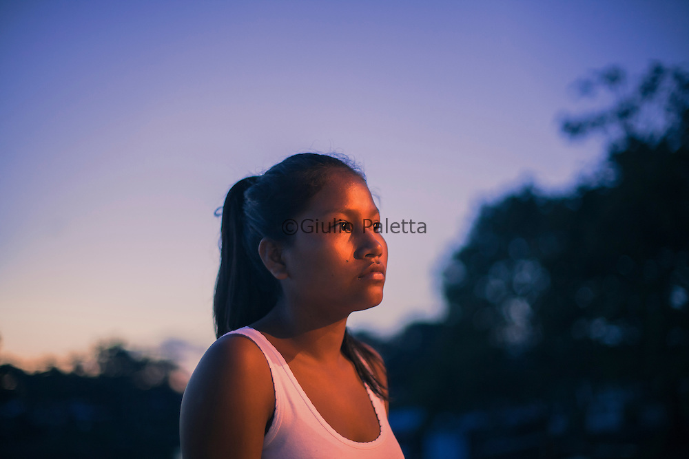 Young girl waiting at Leticia's dock. Leticia, Colombia / Brazil / Peru border