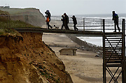 Coastal Erosion, Happisburgh on the North Norfolk coast, Britain. Managed retreat is being allowed to happen at many locations on the coast of Britain. Here at Happisburgh the north sea has destroyed all sea defences, the land has been eroded away by wind and sea and homes, property and WW2 gun emplacements-seen here-have fallen onto the beach from the crumbling cliff edge..The only access point to the beach is down a metal stairway..COPYRIGHT PHOTOGRAPH BY BRIAN HARRIS  © 2008.07808-579804