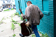 Clifford, a transient alcoholic, carries his new guitar, which was a gift from his friend, in South Buffalo, NY, on Wednesday, July 29, 2009.