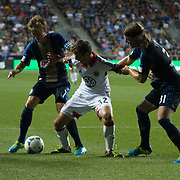 D.C. United Midfielder COLLIN MARTIN (32), (Center) attempts to keep procession of the ball while Philadelphia Union Midfielder BRAIN CARROLL (7) and Philadelphia Union Defender JEFF PARKE (31) attempts to defend in the first half a MLS regular season match against the Philadelphia Union Saturday. August. 10, 2013 at PPL Park in Chester PA.