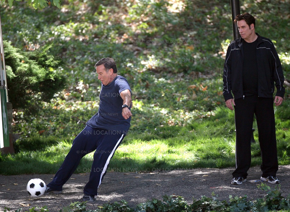 LOS ANGELES, CALIFORNIA - FRIDAY 20TH JUNE 2008 EXCLUSIVE: John Travolta and Robin Williams shooting scenes for their movie 'Old Dogs'. In the scene Robin Williams kicks a ball back to a group of kids while taking a walk in a park with Travolta. The two actors were very funny in between takes. Photograph: On Location News. Sales: Eric Ford 1/818-613-3955 info@OnLocationNews.com