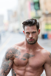 shirtless muscular man with tattoos outdoors