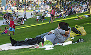 A couple enjoy an afternoon in the park. Watching the crowd and a taste of watermelon are two simple treats. Manhattan Beach, California.
