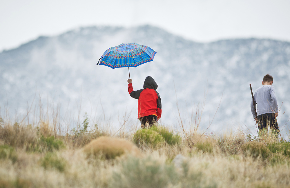 mkb042917a/metro/Marla Brose -- Philip Miletkov, 8, holds an umbrella while walking at Vista Sandia Equestrian Park in northeast Albuquerque with his brother Emil, 11, right, and his father Nikolay Miletkov, Saturday, April 29, 2017. A dusting of snow covered the Sandias. (Marla Brose/Albuquerque Journal)