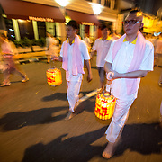 A procession from the Goddess of Mercy Temple to the ocean to release the boat is led by devotees carrying paper lanterns.