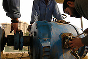 Electrical engineer Hazim Mohammed (R) works to repair a water pump dating from 1935 at the al-Wathba water treatment plant in Baghdad. The failing water infrastructure in Iraq suffers from old equipment and a lack of spare parts due to the UN sanctions.