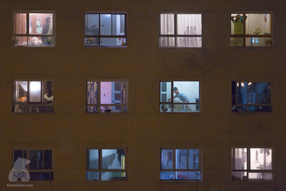 People at home in the evening, Hamhung, North Korea. As I observed the comings and goings of those living in a building on the other side of the hotel where I stayed in Hamhung, I had a sense that I had managed to escape, temporily, the strict rules imposed daily on what I could photograph. For several hours, I peered into the daily life of north koreans preparing dinner, watching Juche TV, hanging their laundry, putting their bike in the living room... These seemingly banal moments are the ones I traveled to the DPRK for, as I wanted to see if I could find slivers of normality untainted by korean propaganda or shaped by western media.