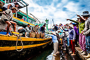 Controlled chaos ensues as fishing boats arrive with a fresh catch and sellers vie for the best selections. Phan Thiet, Vietnam.