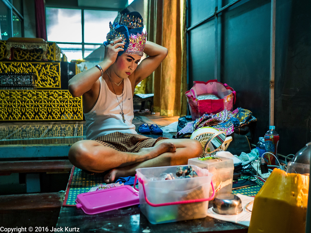 """30 JANUARY 2016 - NONTHABURI, NONTHABURI, THAILAND: A performer gets into character backstage before a """"likay"""" show at Wat Bua Khwan in Nonthaburi, north of Bangkok. Likay is a form of popular folk theatre that includes exposition, singing and dancing in Thailand. It uses a combination of extravagant costumes and minimally equipped stages. Intentionally vague storylines means performances rely on actors' skills of improvisation. Like better the known Chinese Opera, which it resembles, Likay is performed mostly at temple fairs and privately sponsored events, especially in rural areas. Likay operas are televised and there is a market for bootleg likay videos and live performance of likay is becoming more rare.     PHOTO BY JACK KURTZ"""
